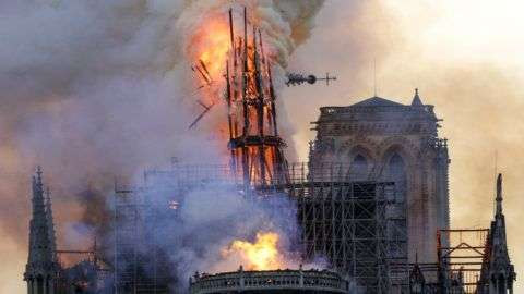 The steeple collapses as smoke and flames engulf the Notre-Dame Cathedral in Paris on April 15, 2019. - A huge fire swept through the roof of the famed Notre-Dame Cathedral in central Paris on April 15, 2019, sending flames and huge clouds of grey smoke billowing into the sky. The flames and smoke plumed from the spire and roof of the gothic cathedral, visited by millions of people a year. A spokesman for the cathedral told AFP that the wooden structure supporting the roof was being gutted by the blaze. (Photo by Geoffroy VAN DER HASSELT / AFP)