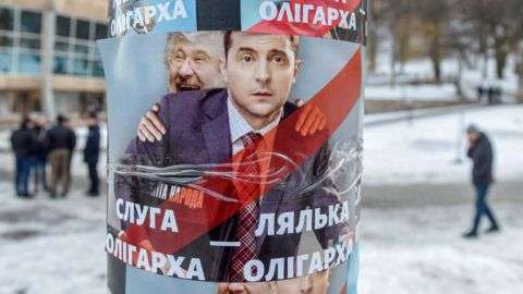 A picture taken on February 8, 2019 shows people walking by placards depicting Ukrainian entertainer and presidential candidate Volodymyr Zelensky and oligarch Ihor Kolomoyskyi, looking out from his back, and reading 'Servant of oligarch, doll of oligarch' is seen glued prior to Zelensky performance in western Ukrainian city of Lviv on February 8, 2019. - Around 20 percent of Ukrainians now say they plan to vote for comedian and film actor Zelensky, putting him several points ahead of his main rivals in opinion polls last week. The 41-year-old entertainer has tapped into popular discontent with the political class and has largely relied on the internet to get his message across. (Photo by YURI DYACHYSHYN / AFP)