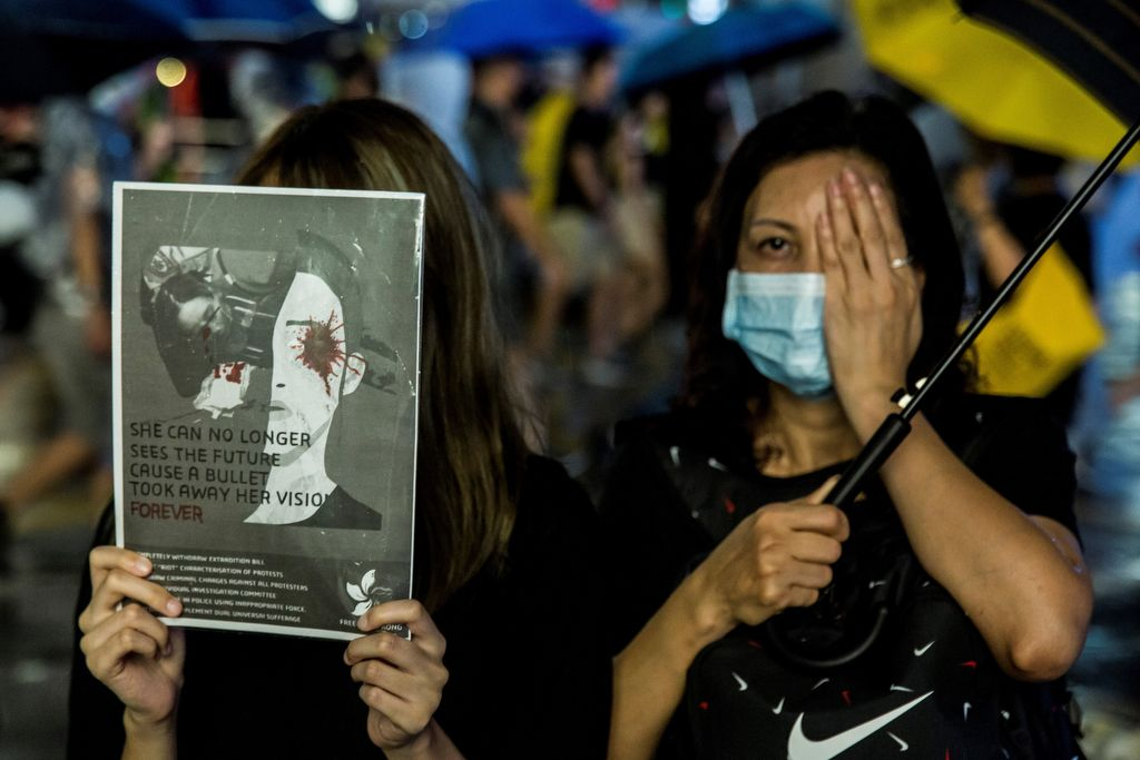 A protester (L) holds a sign and another (R) covers her eye to show solidarity with a woman who suffered an eye injury which demonstrators blamed on a bean-bag round fired by police at a previous rally, during an anti-government rally in Hong Kong on August 18, 2019, in the latest opposition to a planned extradition law that has since morphed into a wider call for democratic rights in the semi-autonomous city. - Hong Kong democracy activists gathered August 18 for a major rally to show the city's leaders their protest movement still attracts wide public support despite mounting violence and increasingly stark warnings from Beijing. (Photo by ISAAC LAWRENCE / AFP)