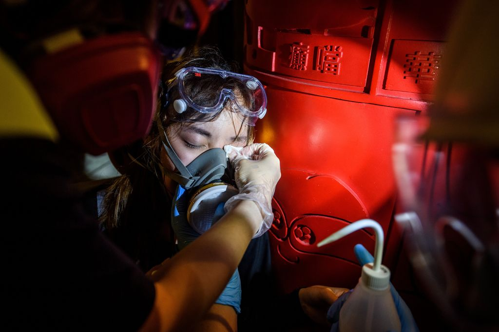 This picture taken on August 3, 2019 shows a woman receiving an eye wash from volunteer medics after she was affected by tear gas during a protest in the Tsim Sha Tsui area of Hong Kong's Kowloon district. - Nurses, doctors, medical students and ordinary people with first aid training have all clamoured to join what has become a small volunteer corps helping treat people on the frontlines of protests that have engulfed the city for over two months. (Photo by ANTHONY WALLACE / AFP) / TO GO WITH HongKong-politics-unrest-China-health,FOCUS by Yan Zhao