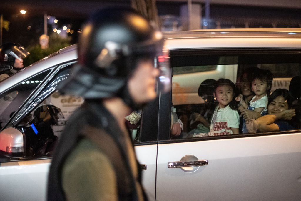 Passengers including children look out from a car as riot police patrol a road in Hong Kong's Kwun Tong district on August 24, 2019, during protests in the latest opposition to a planned extradition law that has since morphed into a wider call for democratic rights in the semi-autonomous city. - Hong Kong riot police on August 24 fired tear gas and baton-charged protesters who retaliated with a barrage of stones, bottles and bamboo poles, as a standoff in a working-class district descended into violence. (Photo by Philip FONG / AFP)