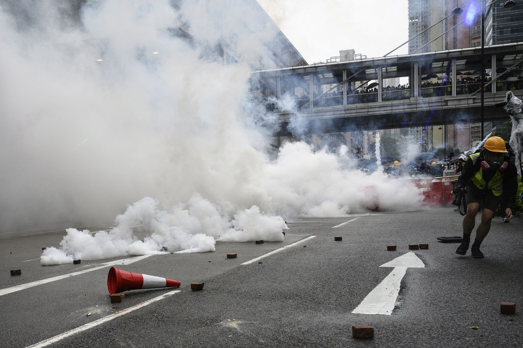 Protesters return tear gas towards the police in Tseun Wan in Hong Kong on August 25, 2019 in the latest opposition to a planned extradition law that has since morphed into a wider call for democratic rights in the semi-autonomous city. - Hong Kong police used water cannon for the first time and at least one officer fired his sidearm during pitched battles with protesters on August 25, one of the most violent nights in three months of pro-democracy rallies that have rocked the city. An afternoon rally in the district of Tsuen Wan spiralled into violent running confrontations between protesters and police, with officers several times caught outnumbered and isolated by masked youths wielding sticks and throwing rocks. (Photo by Philip FONG / AFP)