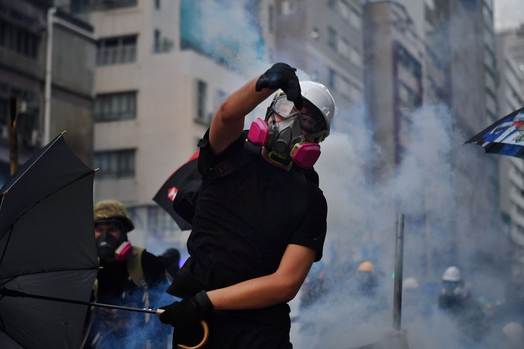 A protester throws back a tear gas canister during clashes with riot police at Kowloon Bay in Hong Kong on August 24, 2019, in the latest opposition to a planned extradition law that has since morphed into a wider call for democratic rights in the semi-autonomous city. - Hong Kong riot police on August 24 fired tear gas and baton-charged protesters who retaliated with a barrage of stones, bottles and bamboo poles, as a standoff in a working-class district descended into violence. (Photo by Lillian SUWANRUMPHA / AFP)