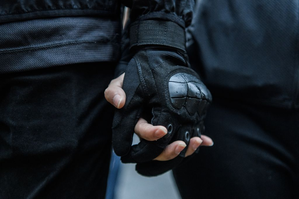 In this picture taken on August 25, 2019, Abby (R), 19, and her boyfriend Nick, 20, holds hands during a protest in Tsuen Wan, an area in the New Territories in Hong Kong. - A gas mask lovingly adjusted, a hand squeezed before approaching police linesand a frantic search through swirls of tear gas -- Abby and Nick's relationship has blossomed on the barricades during Hong Kong's long summer of protest. (Photo by Anthony WALLACE / AFP) / TO GO WITH AFP STORY HONG KONG-POLITICS-CHINA-UNREST-PROTEST,FOCUS BY AIDAN JONES AND JASMINE LEUNG