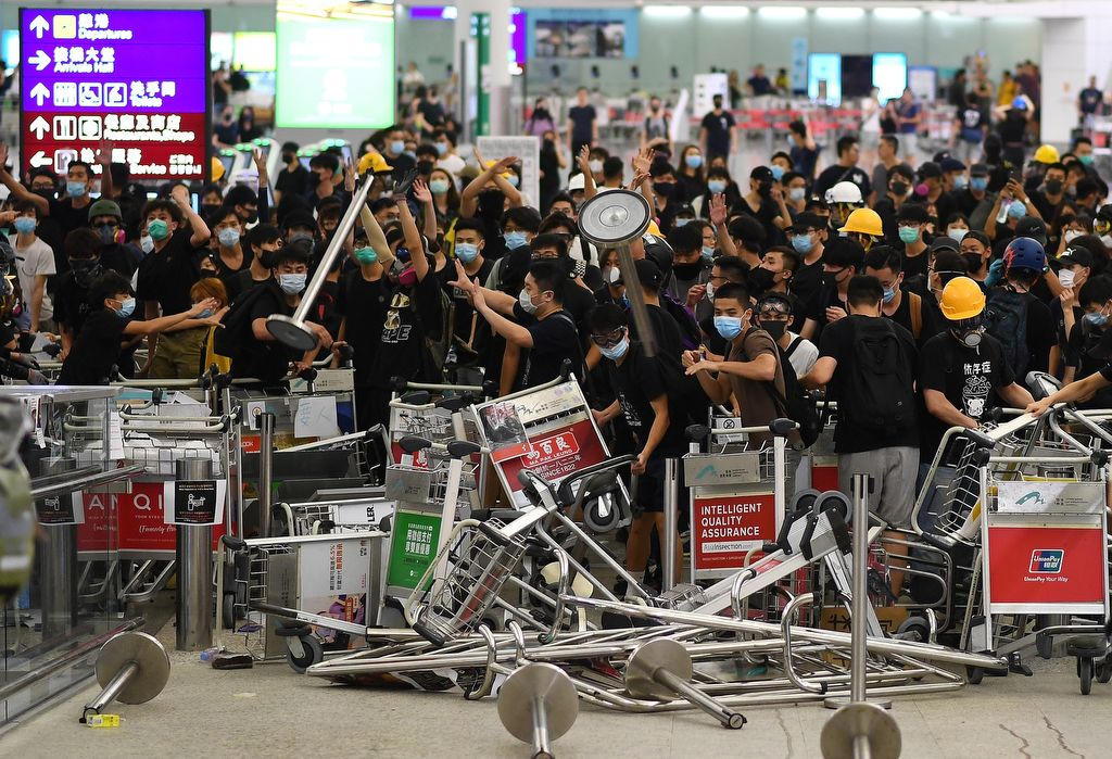 """Pro-democracy protestors block the entrance to the airport terminals after a scuffle with police at Hong Kong's international airport late on August 13, 2019. - Hundreds of flights were cancelled or suspended at Hong Kong's airport on August 13, 2019 as pro-democracy protesters staged a second disruptive sit-in at the sprawling complex, defying warnings from the city's leader who said they were heading down a """"path of no return"""". The new protest came as Beijing sent further ominous signals that the 10 weeks of unrest must end, with state-run media showing videos of security forces gathering across the border. (Photo by Manan VATSYAYANA / AFP)"""
