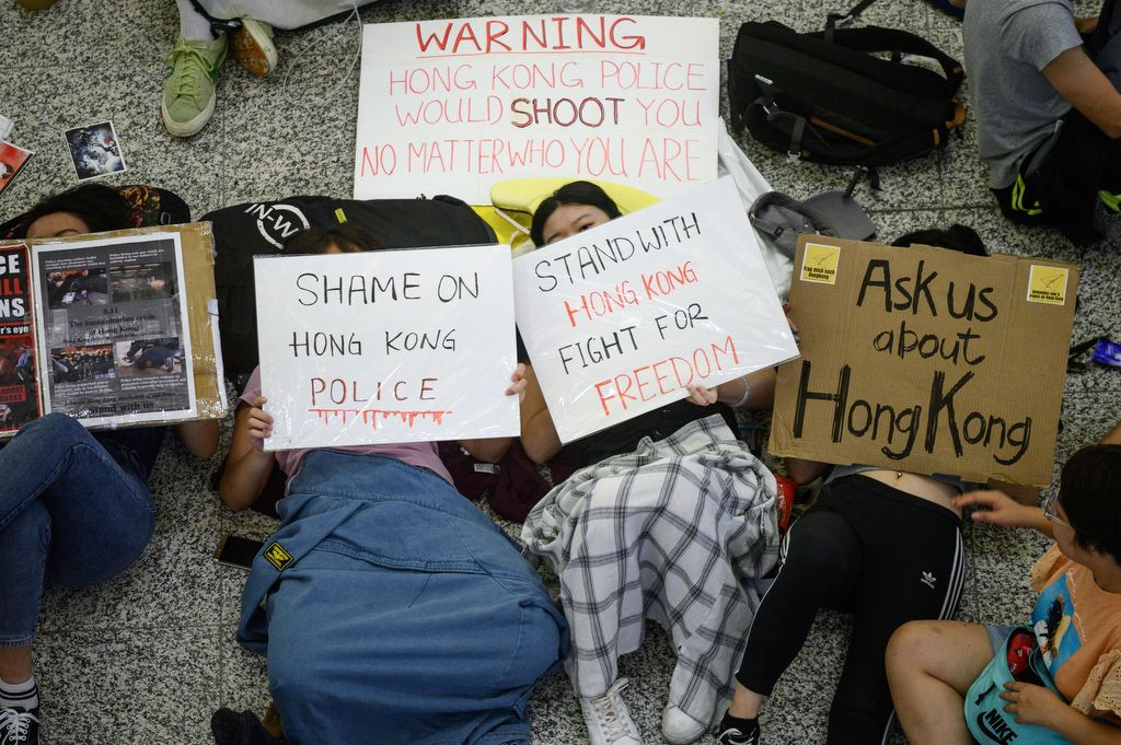 Protesters hold placards as they rest on the floor of Hong Kong's international airport on August 14, 2019. - Flights were departing Hong Kong airport largely on schedule morning on August 14, a day after pro-democracy protesters caused chaos with a disruptive sit-in that paralysed the busy transport hub. (Photo by Philip FONG / AFP)