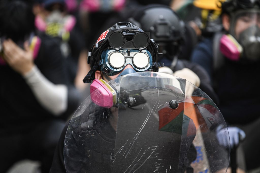 A protester looks on from the front line during a protest in Kowloon Bay in Hong Kong on August 24, 2019, during the latest opposition to a planned extradition law that has since morphed into a wider call for democratic rights in the semi-autonomous city. - Hong Kong riot police on August 24 fired tear gas and baton-charged protesters who retaliated with a barrage of stones, bottles and bamboo poles, as a standoff in a working-class district descended into violence. (Photo by ANTHONY WALLACE / AFP)