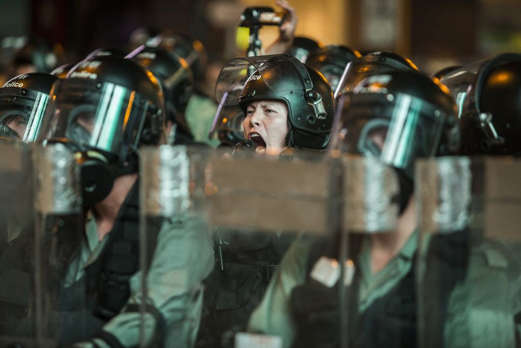 Riot police shout warnings to protesters in the Mong Kok district of Hong Kong on August 3, 2019, in the latest opposition to a planned extradition law that has quickly evolved into a wider movement for democratic reforms. - Anti-government protesters in Hong Kong erected barricades in a popular shopping district and blocked a major tunnel on the evening of August 3, defying increasingly stern warnings from China over weeks-long unrest that has plunged the city into crisis. (Photo by ISAAC LAWRENCE / AFP)