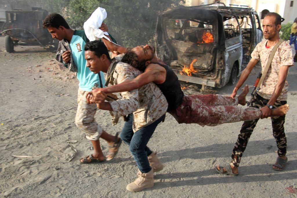EDITORS NOTE: Graphic content / Yemenis carry a wounded man past a burning vehicle following a reported suicide car bombing in Huta, the capital of the southern province of Lahj, a bastion of Al-Qaeda jihadists, on March 27, 2017. - Ten jihadists, including a suicide bomber, perished when they attacked a government building in southern Yemen, killing six soldiers and four civilians, officials said. (Photo by SALEH AL-OBEIDI / AFP)