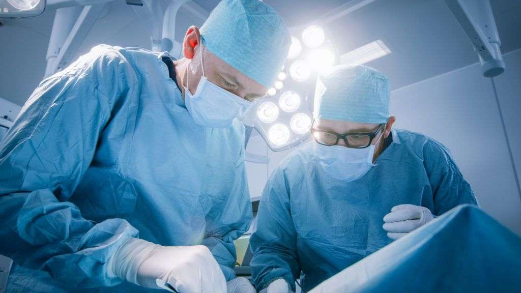 Low Angle Shot In Operating Room of Two Surgeons During the Surgery Procedure Bending Over Patient with Instruments. Professional Doctors in Modern Hospital